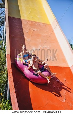 Happy Young Couple Sitting In A Circle, Inflatable Water Wheel. Roll With A Water Slide In The Pool