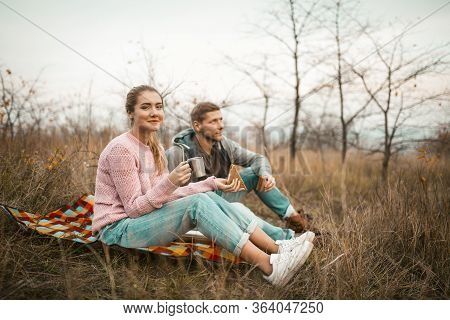 Young Men And Women Have Picnic Outdoors, Couple Of Travelers Eat Snacks And Drink A Hot Drink, Rest