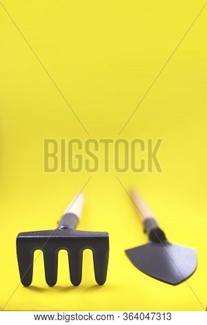 Gardening Tools On Yellow Background. The Concept Of Environmental Stewardship And World Environment