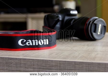 Brecht, Belgium - April 30 2020: A Close Up Portrait Of A Blurred Canon Dslr Camera On A Wooden Tabl