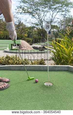 Man Making A Mini Golf Putt Wearing Protective Gloves