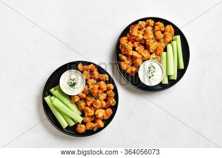 Cauliflower Buffalo Wings With Celery And Sauce On Plate Over White Stone Background With Free Text