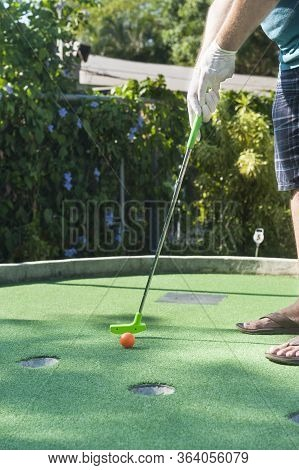 Man Making A Mini Golf Putt With Latex Gloves On Outside In The Summer