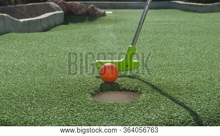 Green Mini Golf Putter Ready To Tap An Orange Ball Into The Hole On Green Turf