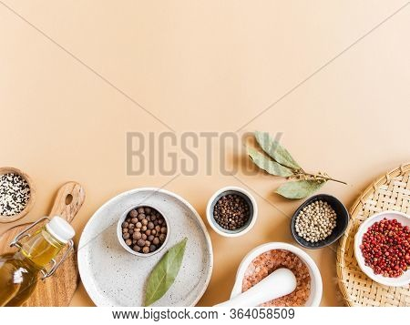 Flat Lay Of Small Bowls Various Dry Spices, Wood Kitchen Utensils, Olive Oil In Glass Bottle On A Be