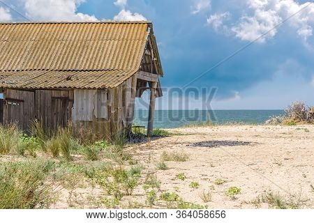 Landscape With An Old Rickety Barn On The Beach Against The Background Of The Sea And Thunderclouds,