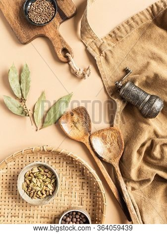 Kitchen Flat Lay Of Beige Apron, Small Bowls With Spices, Metal Spice Mill, Wood Kitchen Utensils On