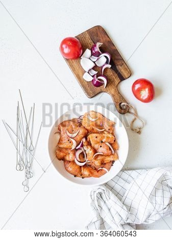 Raw Marinated Pork Meat With Spices In A White Bowl, Fresh Vegetable And Metal Skewers. Marinating M