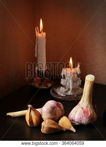 Retro Country Style Still Life With Garlic Bulbs And  Two Candlesticks With Burning Candles Against