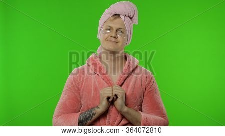 Portrait Of Young Transsexual Man Wearing Pink Bathrobe And Towel On His Head Looking In The Mirror