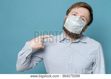 Man Points Index Finger To The Medical Mask On His Face, Which Is Not Snug Due To The Shaggy Beard.