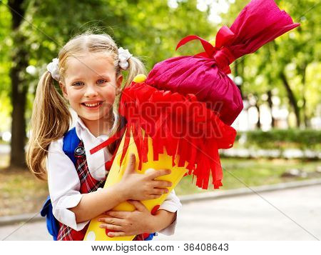 Child holding gift school cone. Isolated.