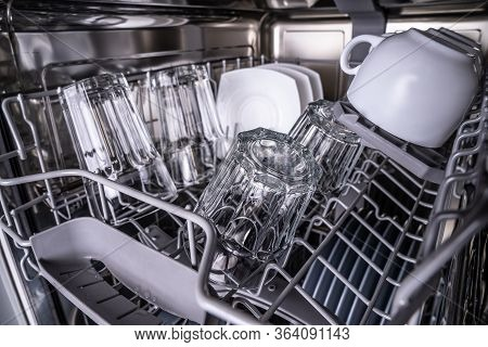 Set Of Clean Dish In Dishwasher. Glowing Transparent Glasses And White Cups After Washing In Dishwas