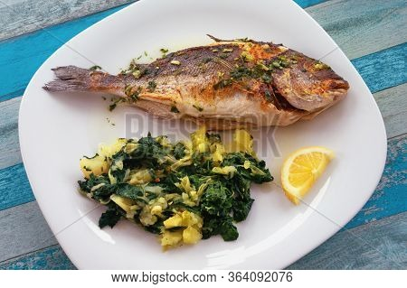 Balkan Cuisine. Grilled Fish ( Sea Bream ) With Green Leafy Vegetables On White Plate. Flat Lay, Rus