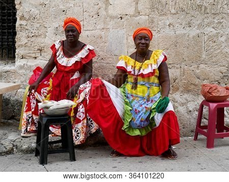 Cartagena, Colombia, August 1 2019: Two Tipical Fruit Street Sellers Palenqueras With Colorful Dress