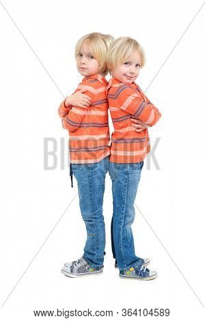Two caucasian boys twins brothers posing in studio isolated on white