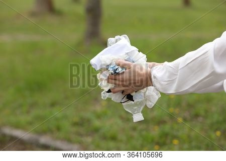 Woman Throws Plastic Garbage In The Trash. Woman Hand Picking Up Garbage Plastic For Cleaning At Par