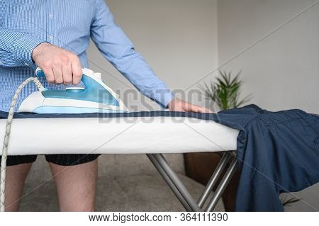 A Man In A Blue Dress Shirt And Bare Legs, Ironing His Trousers On An Ironing Board. Copy Space.