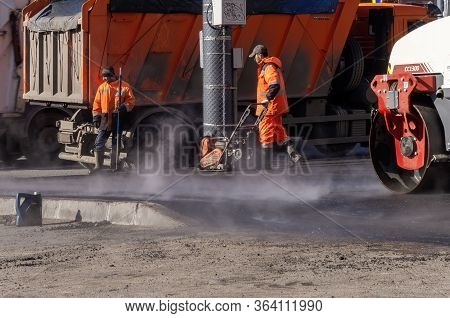 Saint-petersburg, Russia, April 2020: Road Workers In Orange Uniforms Making New Paving Near Paver A