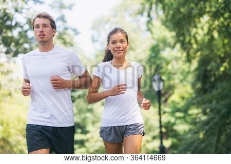 Run race runners exercising together in city park walking for charity benefit wearing white t-shirts. Sport fitness friends running together outdoor. Healthy active lifestyle Asian woman man couple.