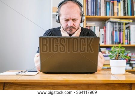 Man Working From Home Office, Worried Face Expression. Adult Bearded Man With Headphones Looking Wor