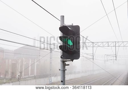 Hazy Landscape - Railway Tracks Hiding In The Fog, In The Foreground The Led Railway Signal Is Green