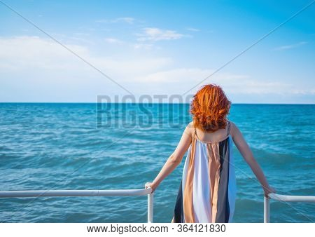 Woman Standing On The Pier At The Railing At Sunrise And Looks Towards The Ocean And The Horizon