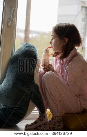 The Little Girl Is Drinking Yogurt. Girl Drinks Yogurt. Cute Little Girl Drinking Yogurt At Home.die