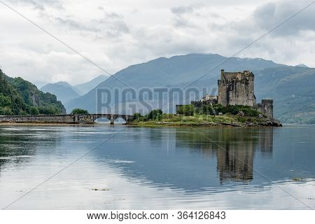 Reflection Of Eilean Donan Castle, Scotland, Uk And The Bridge In Waters Of Loch Duich In Typical Sc