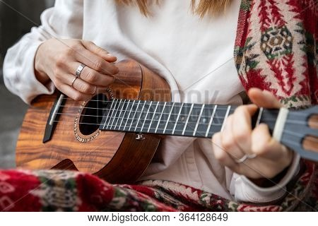 Woman Playing Hawaiian Guitar, Sings A Song On Vintage Ukulele At Home. Selective Focus. Close Up.