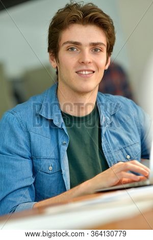 Portrait of smiling student working from home on laptop
