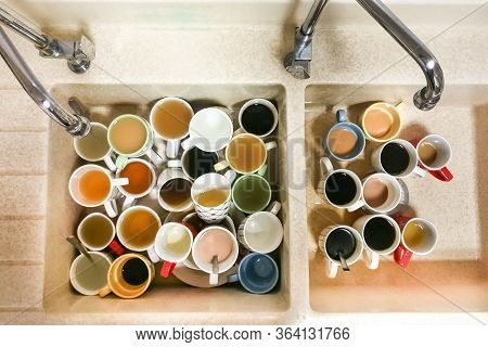 Dirty Pile Of Unwashed Cups And Mugs In Wash Basin