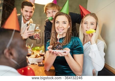 Friends at a party celebrate their birthday and are photographed with cake