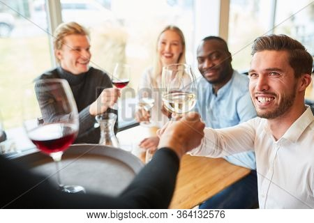 Waitress serves young people as guests in the restaurant and serves wine