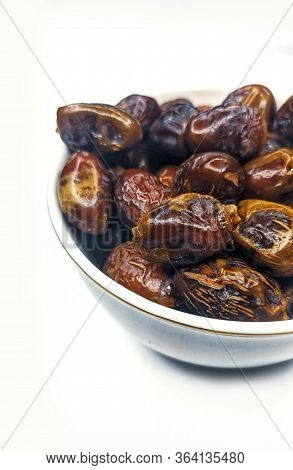 Showing Date Palm Fruit In A White Bowl On White Background.the Samples Of Ripped And Stored Fruit O