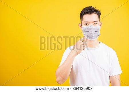 Asian Young Teen Man Wearing Surgical Hygienic Protective Face Mask Against Coronavirus And Pointing