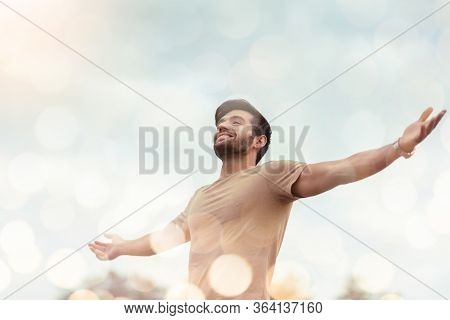 Happy Traveler Male Embracing Life And Enjoying Freedom With Open Arms Over Sky And Bokeh Effect. Ca