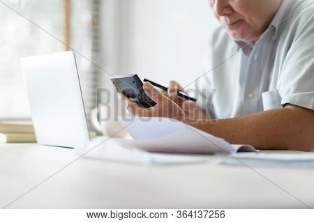 Stressed Asian Old Man Using Calculator For Calculate Family Budget, Monthly Expenses In Home During