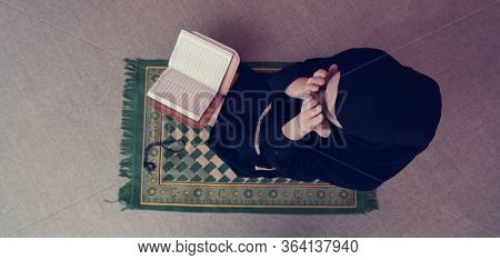 Middle eastern woman praying and reading the holy Quran (public item of all muslims). Education concept of Muslim woman studying The holy Quran at home or mosque in ramadan month.