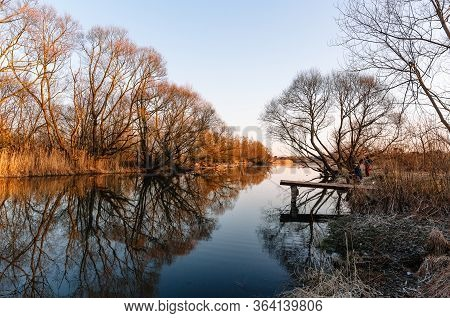 A Beautiful Blue River With A Bridge Along Bushes And Trees In The Rays Of Orange Sunlight. Reflecti