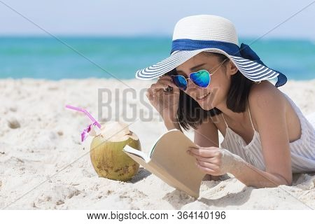 Summer Time Woman Vacation On The Beach. Cheerful Woman Wear Summer Dress And Straw Hats Sitting On