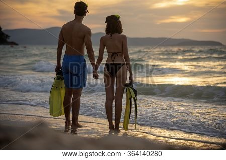 Couple Lover Holding Hands Together On The Beach During Sunset On Honeymoon Trip At Tropical Summer