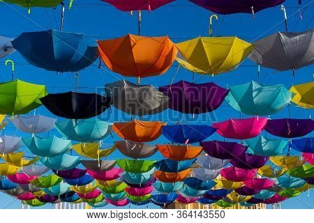 Colorful Vibrant Umbrellas Hanging Over The Walking Street For A Festival On A Blue Sky Sunny Day