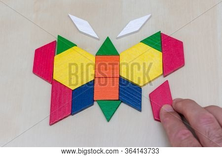 Tangram Butterfly Colored Child Geometric Puzzle Piece With Hand Filling In Final Piece On Brown Bac