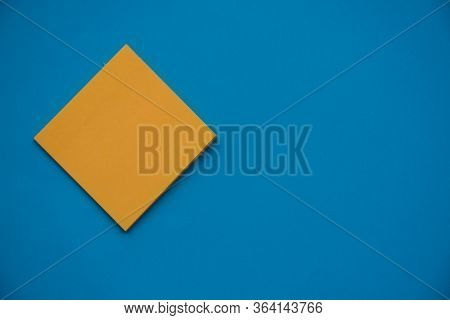 Bright Orange Posted Note On Bright Blue Flat Lay Background For Education Or Business Organization