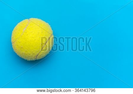 Bright Yellow Tennis Ball On A Solid Aqua Blue Flat Lay Background Symbolizing Sports And Activity W
