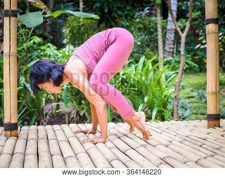 Yoga Practice Outdoor. Asian Yoga Teacher Preparing For Bakasana, Crow Pose. Balancing Asana In Hath