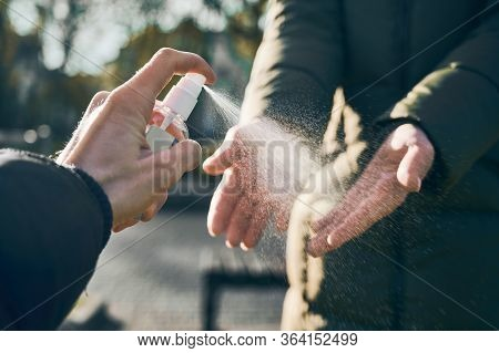 Cropped Close-up Snapshot Of Males Hand Spraying Sanitizer On Womans Hands Outdoors To Disinfect Han