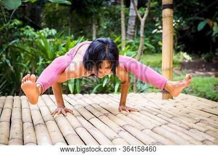 Yoga Practice Outdoor. Asian Yoga Teacher Practicing Titibasana, Firefly Pose. Strong Core Arm Balan