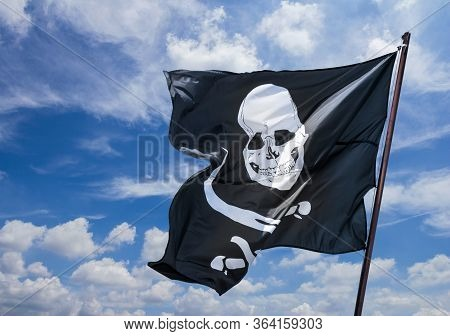 Pirates Flag In The Wind, Depicting The Skull And Crossbones As A Symbol Of Pirates. Pirate Flag Aga